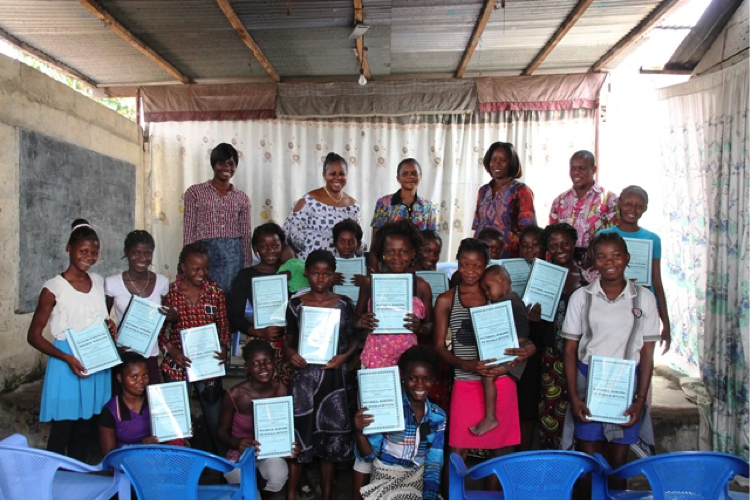 Women and female children holding curriculum books proudly in a classroom.
