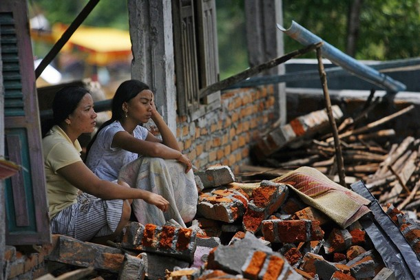 Nepalese women sitting on rubble.